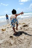 Ein kleiner Junge, der in den Ozean läuft Stockbilder