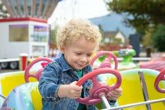 Ein kleiner Junge, der in einem Spaßmessekarussell spielt Stockfoto