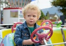 Ein kleiner Junge, der in einem Spaßmessekarussell spielt Lizenzfreie Stockfotos