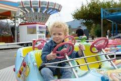 Ein kleiner Junge, der in einem Spaßmessekarussell spielt Lizenzfreie Stockfotografie