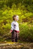 Ein kleiner Junge, der im Wald spielt Lizenzfreie Stockfotos