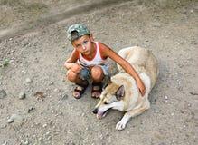 Ein kleiner Junge, der nahe bei großem Hund sitzt Stockfotos