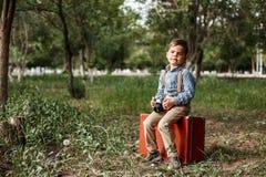 Ein kleiner Junge in der Weinlesekleidung sitzt auf einem alten Koffer mit einer Retro- Kamera in seinen Händen stockbilder