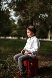 Ein kleiner Junge in der Weinlesekleidung sitzt auf einem alten Koffer mit einer Retro- Kamera in seinen Händen stockfoto