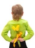 Ein kleiner Junge, der zurück gelbe Tulpen hinter seinem anhält Lizenzfreies Stockbild