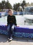 Ein kleiner Junge in einer grünen Strickjacke sitzt nahe einem großen Brunnen im Park und untersucht die Kamera lizenzfreies stockfoto