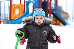 Ein kleiner Junge geht in den Schnee im Winter auf dem Hintergrund eines Spielplatzes lizenzfreies stockfoto