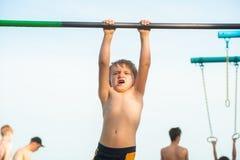 Ein kleiner Junge hängt an der horizontalen Stange und kann alles nicht tun stockfotos
