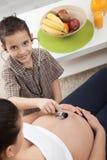 Ein kleiner Junge hört auf einen Stethoskopbauch seiner schwangeren Mutter Lizenzfreie Stockfotos