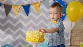 Ein kleiner Junge haftet seine Finger innerhalb eines Kuchens stock video footage