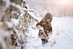 Ein kleiner Junge im Pelz, draußen spielend im Winter Snowy-Wald lizenzfreies stockfoto