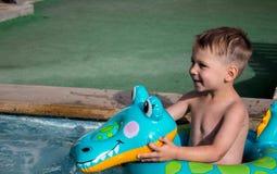 Ein kleiner Junge im Pool auf einem aufblasbaren Schoss lizenzfreie stockfotografie