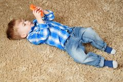 Ein kleiner Junge liegt auf dem Teppich und spielt im Telefon Kleiner Junge, der Smartphone verwendet lizenzfreie stockbilder