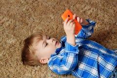 Ein kleiner Junge liegt auf dem Teppich und spielt im Telefon Kleiner Junge, der Smartphone verwendet stockfoto