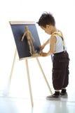 Ein kleiner Junge malt den hölzernen Mann Lizenzfreie Stockfotografie