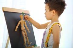 Ein kleiner Junge malt den hölzernen Mann Lizenzfreie Stockbilder