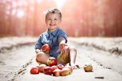 Ein kleiner Junge mit Äpfeln Lizenzfreie Stockbilder
