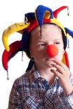 Ein kleiner Junge mit einem Clownwekzeugspritzenclown in einem Hut Lizenzfreie Stockfotos