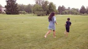Ein kleiner Junge mit einem Mädchen, das auf dem Gras lächelt und springt in eine gute Laune läuft stock footage