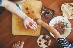Ein kleiner Junge mit seiner Mutter, die zusammen eine Frühstücksmutter und -sohn schmieren Schokoladencreme, um Pfannkuchen zu v lizenzfreies stockbild