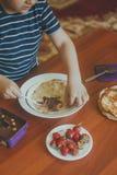 Ein kleiner Junge mit seiner Mutter, die zusammen eine Fr?hst?cksmutter und -sohn schmieren Schokoladencreme, um Pfannkuchen zu v stockfotografie