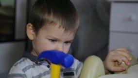 Ein kleiner Junge repariert eine Tabelle mit einem Spielzeughammer stock footage