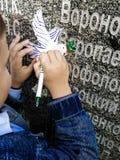 Ein kleiner Junge schreibt auf eine Taube, die vom Papier herausgeschnitten wird stockbilder