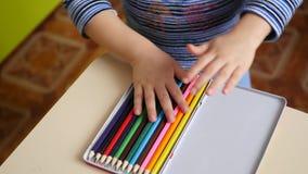Ein kleiner Junge setzt die farbigen Bleistifte in einen Kasten ein Nahaufnahme stock video
