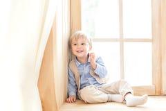 Ein kleiner Junge sitzt auf dem Fensterbrett in der Kindertagesstätte Das Konzept der Freizeit, der Freizeit, der Leute und des L stockfoto
