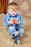 Ein kleiner Junge sitzt auf dem Teppich und spielt im Telefon lizenzfreie stockbilder