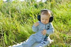 Ein kleiner Junge sitzt auf einer Wiese mit Kopfhörern Stockfotos