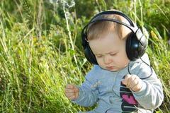 Ein kleiner Junge sitzt auf einer Wiese mit Kopfhörern Lizenzfreie Stockfotos