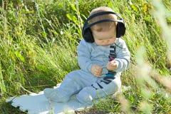 Ein kleiner Junge sitzt auf einer Wiese mit Kopfhörern Stockfotografie
