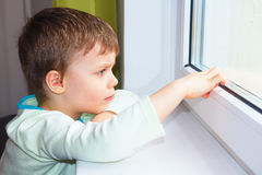 Ein kleiner Junge sitzt am Fenster und untersucht den Abstand Lizenzfreie Stockbilder