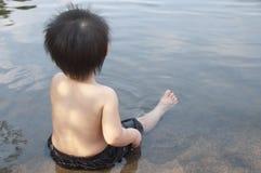 Ein kleiner Junge sitzt im Wasser Stockfotografie