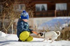 Ein kleiner Junge spielt mit einem Hund auf dem Schnee draußen Stockfotografie