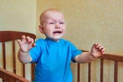 Ein kleiner Junge steht in der Krippe, schreit und ruft Mutter an lizenzfreies stockbild