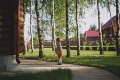 Ein kleiner Junge steht nahe bei einem hölzernen Landhaus, das durch Bäume umgeben wird Lizenzfreie Stockfotografie