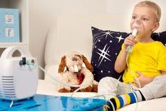 Ein kleiner Junge tut Einatmung mit einem Zerstäuber Eine Hauptbehandlung lizenzfreies stockfoto