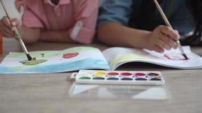 Ein kleiner Junge und eine Farbe des kleinen Mädchens mit Farbe auf dem Album, das auf dem Boden liegt Nahaufnahme stock video footage