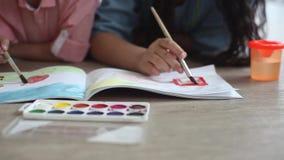 Ein kleiner Junge und eine Farbe des kleinen Mädchens mit Farbe auf dem Album, das auf dem Boden liegt Nahaufnahme HD stock footage