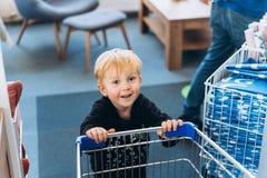 Ein kleiner Junge und ein großer Wagen im Supermarkt lizenzfreie stockfotografie