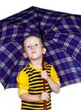 Ein kleiner Junge unter einem Regenschirm Lizenzfreie Stockfotografie