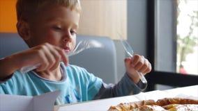 Ein kleiner Junge von vier Jahren schneidet eine Pizza mit einem Plastikmesser stock video