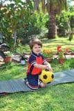 Ein kleiner Junge wirft auf einem grünen Rasen auf Stockfotos