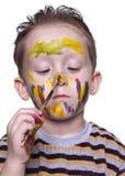 Ein kleiner Junge zeichnet auf die Wekzeugspritze mit einem Pinsel Stockbilder