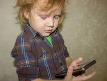 Ein kleiner Kleinkindjunge hält ein Gerät in seinen Händen und klickt an den Smartphoneschirm stockfotos