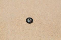 Ein kleiner Kompass, Strand, Sand, Runde, Nord, Süd, Ost, West, rot, schwarz, weiß, Richtung, Orientierung Lizenzfreies Stockfoto