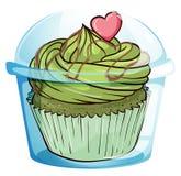 Ein kleiner Kuchen mit einer grünen Zuckerglasur und einem rosa Herzen Lizenzfreies Stockfoto