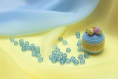 Ein kleiner Kuchen und zerstreute Perlen Stockfotografie
